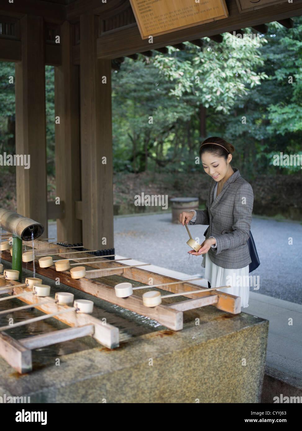 Schöne junge Japanerin besuchen Meiji Jingu Schrein, Tokyo am Reinigung Trog (Chōzuya oder Temizuya) Stockfoto