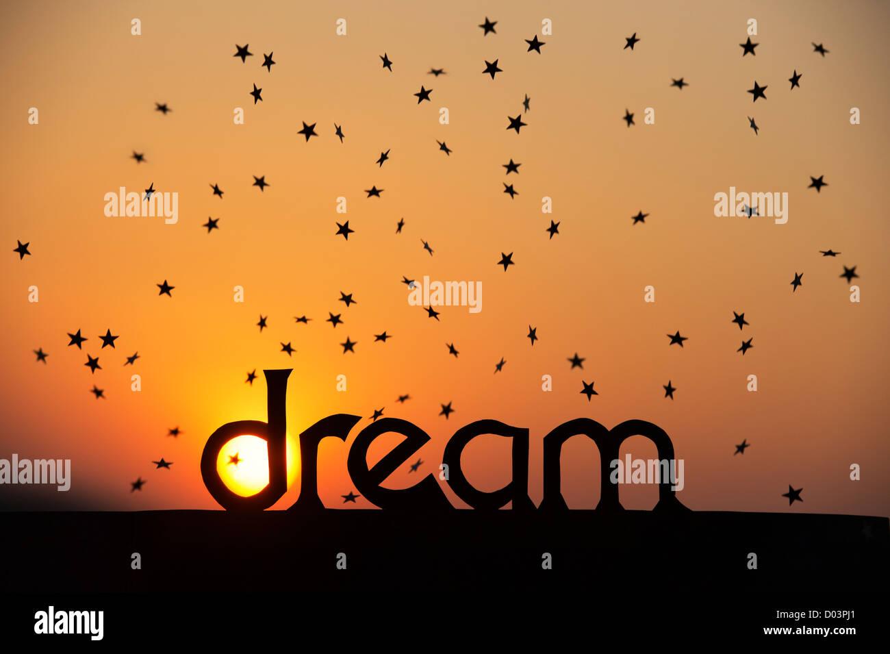 Silhouette Traum Wort und Sternschnuppen bei Sonnenuntergang mit Sonne im D Stockbild