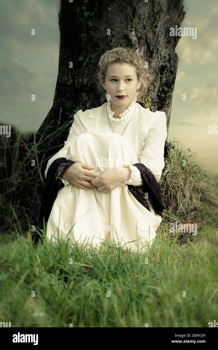 eine Mädchen in einem viktorianischen Kleid sitzt unter einem Baum Stockbild
