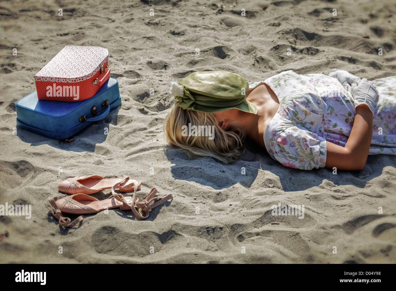 eine Frau in einem geblümten Kleid liegt an einem Strand neben Schuhen und zwei Vintage Koffer Stockbild