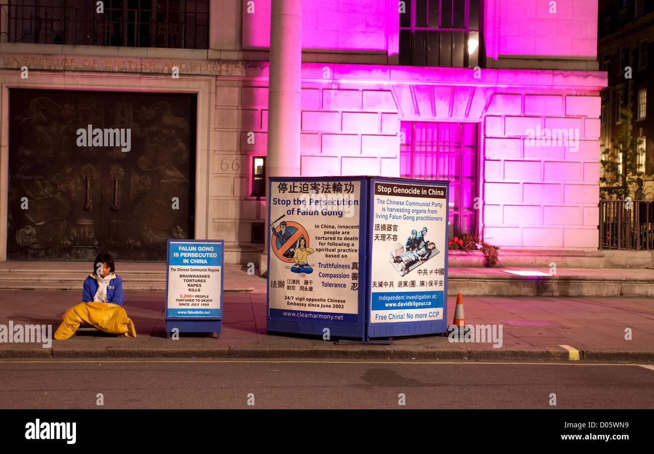 Falun Gong Demonstrant sitzt auf dem Bürgersteig vor der chinesischen Botschaft in Portland Place, London, Stockbild