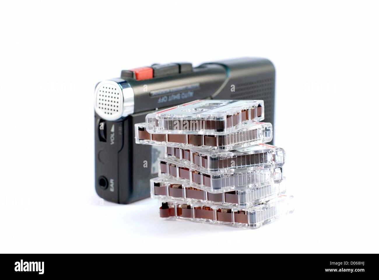 Diktiergerät auf weißem Hintergrund mit einem Stapel von Datensätzen Stockbild