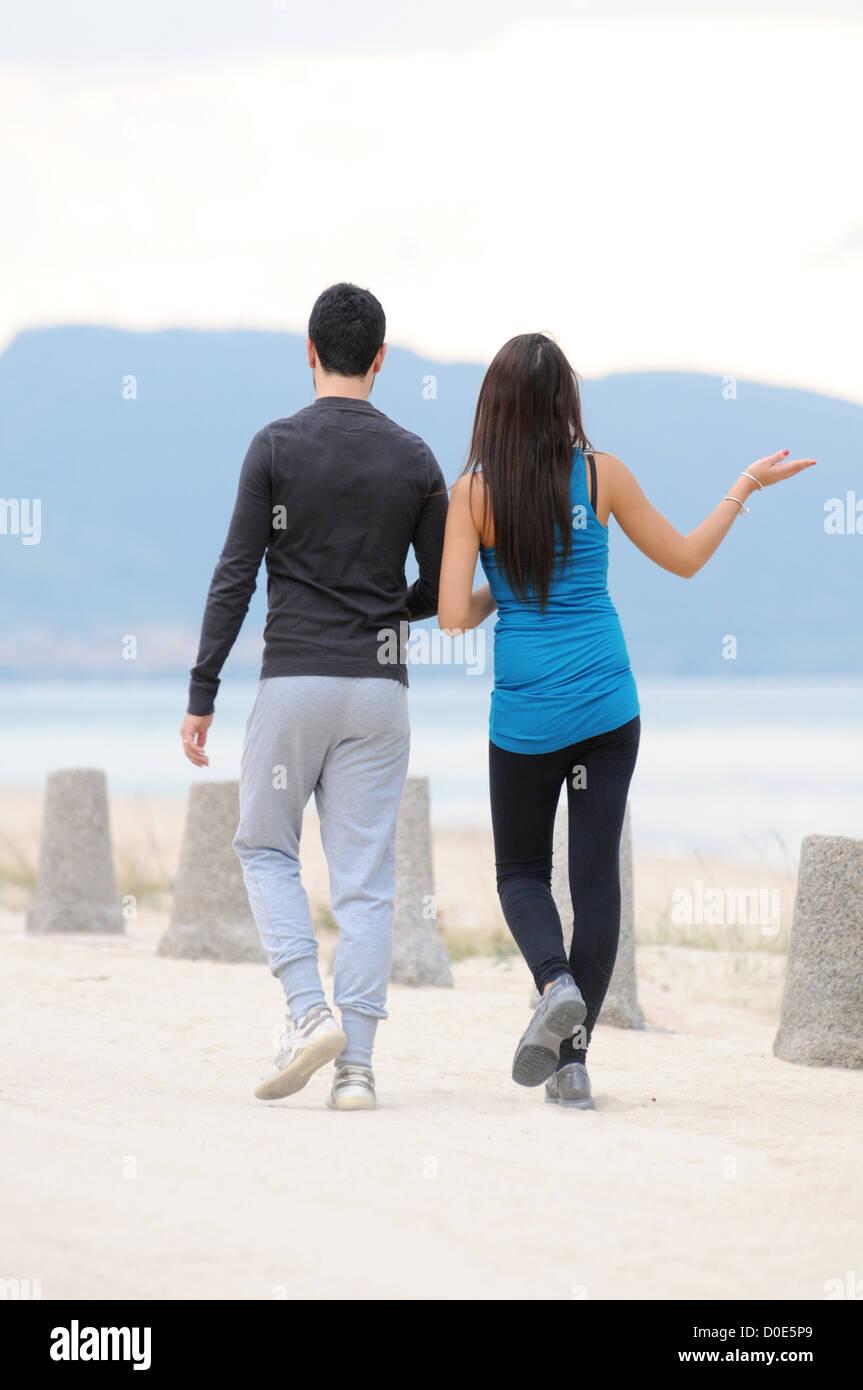 Junges Paar zu Fuß am Strand Stockfoto
