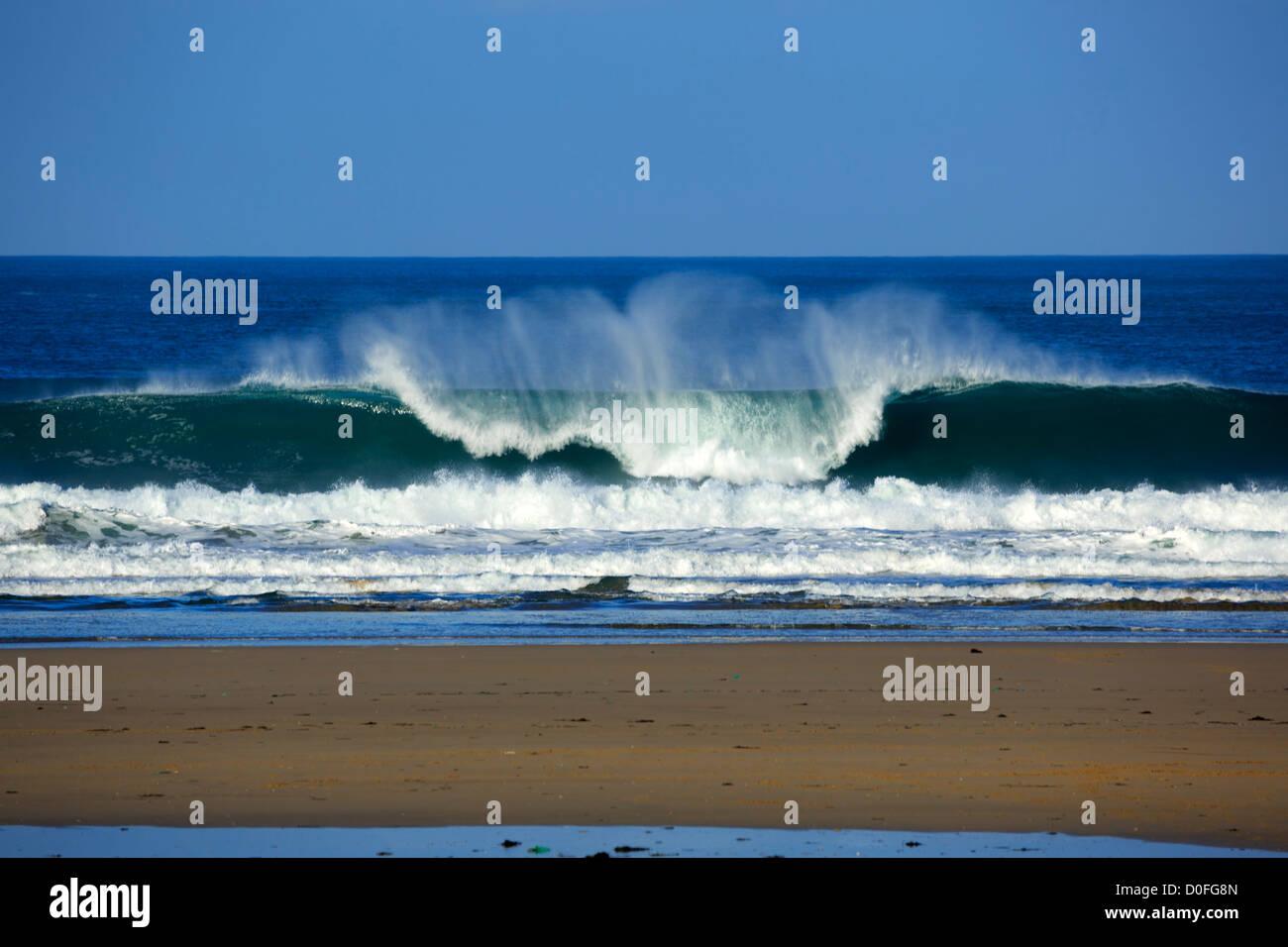 Portreath, Cornwall. Eine Welle bricht am Strand. Stockbild