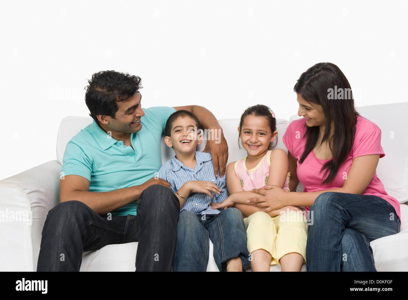 Familie auf einer Couch sitzen und Lächeln Stockfoto