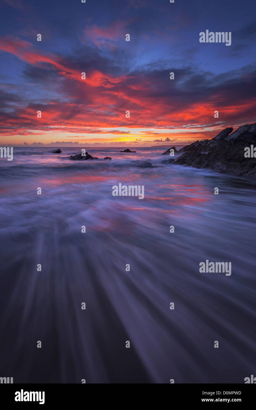 Einen herrlichen Sonnenuntergang und Blei in Linien an Sharrow Punkt, Whitsand Bay, Cornwall Stockbild