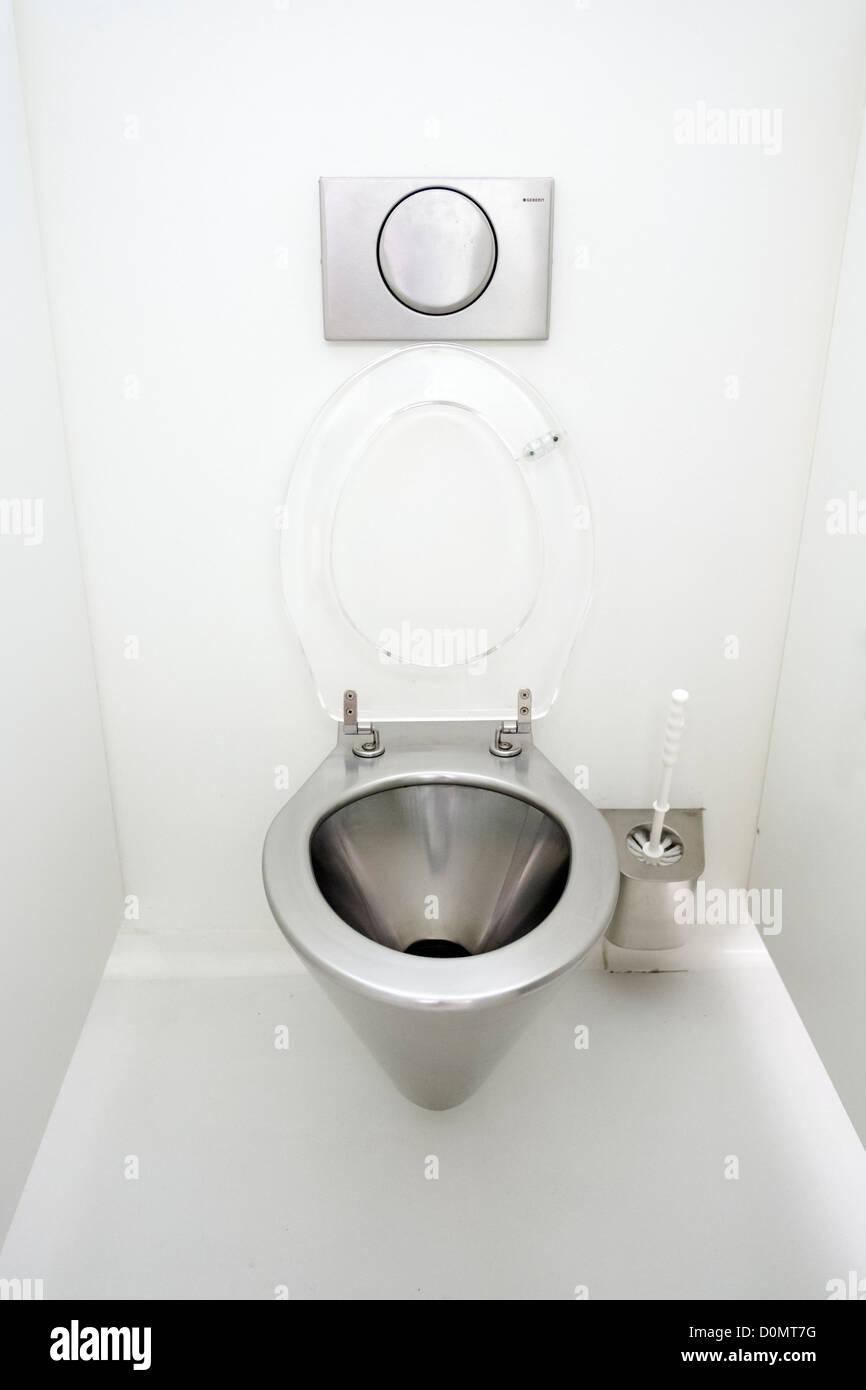 Moderne Edelstahl-WC-Schüssel und Armaturen in WC-Kabine Stockbild