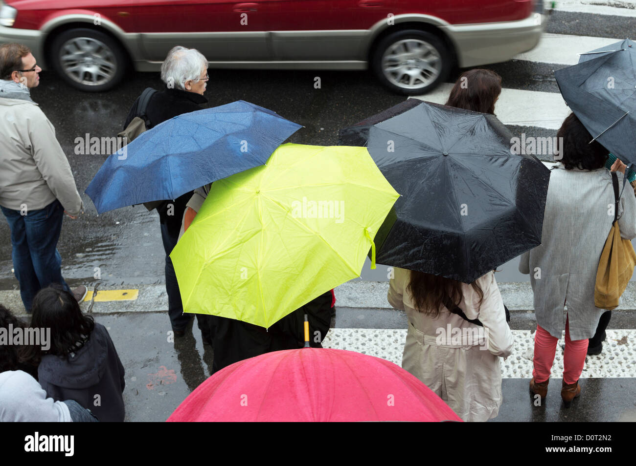 Paris, Frankreich: Fußgänger mit Sonnenschirmen auf einer Stadtstraße im Regen. Stockbild
