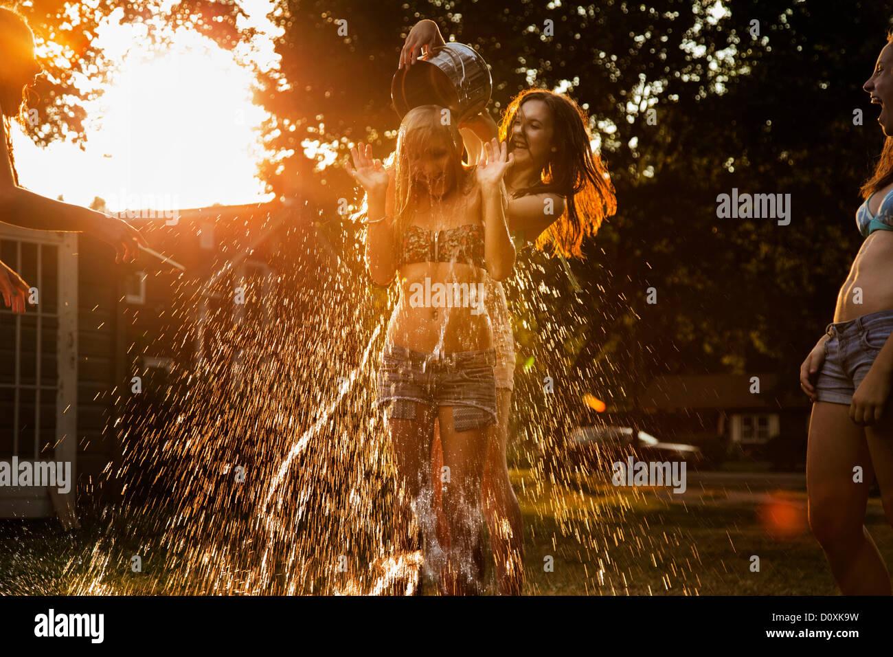 Eimer Wasser in Strömen über Freundes Kopf Mädchen Stockbild