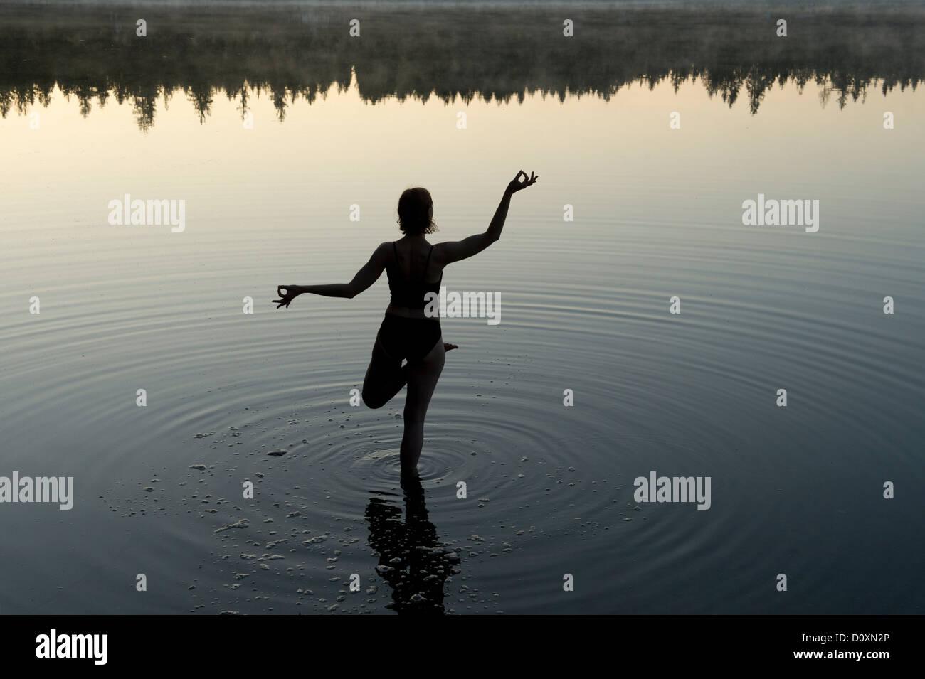 Frau in Yoga-Pose in See Stockbild