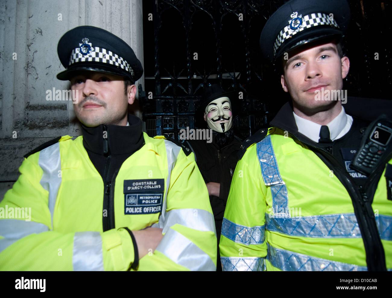 """Ein Demonstrant """"Anonymous"""" steht hinter Polizei Polizisten außerhalb der Houses of Parliament während Stockbild"""