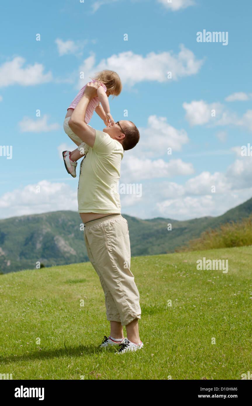 Vater und Kind liegen auf dem Rasen über die Hügel im Hintergrund Stockbild