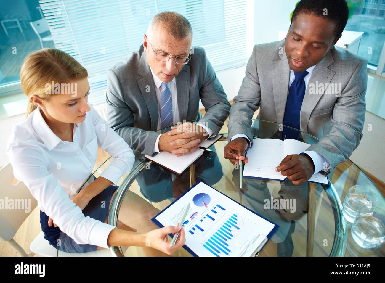 Porträt von hübschen Sekretärin zeigt auf Papier etwas zu ihrem Chef und Kollegen zu erklären Stockfoto
