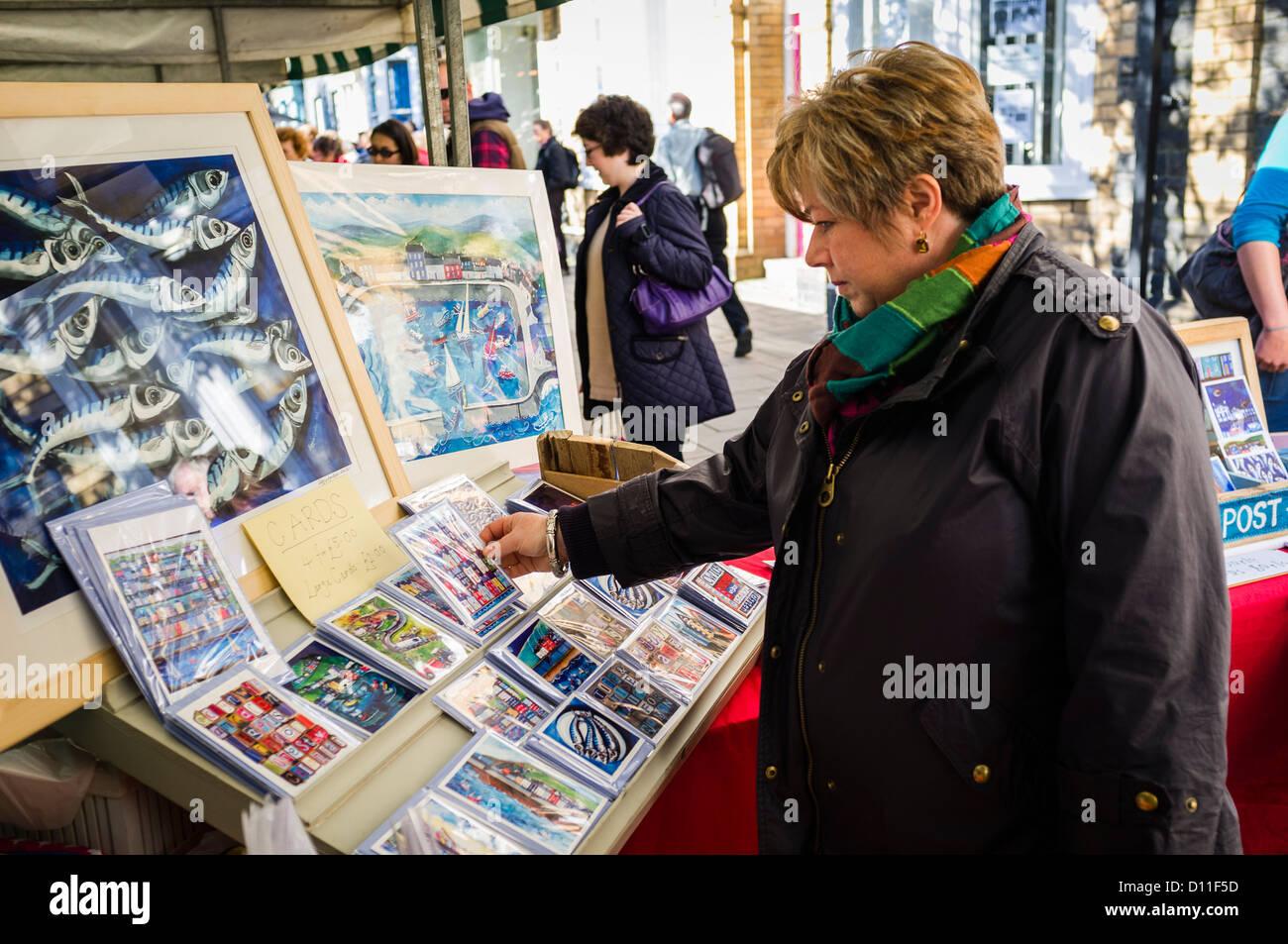 Eine Frau suchen und kaufen, Zeichnungen und Druckgrafiken zum Verkauf an Straßenmarkt Aberystwyth, Wales UK Stockbild
