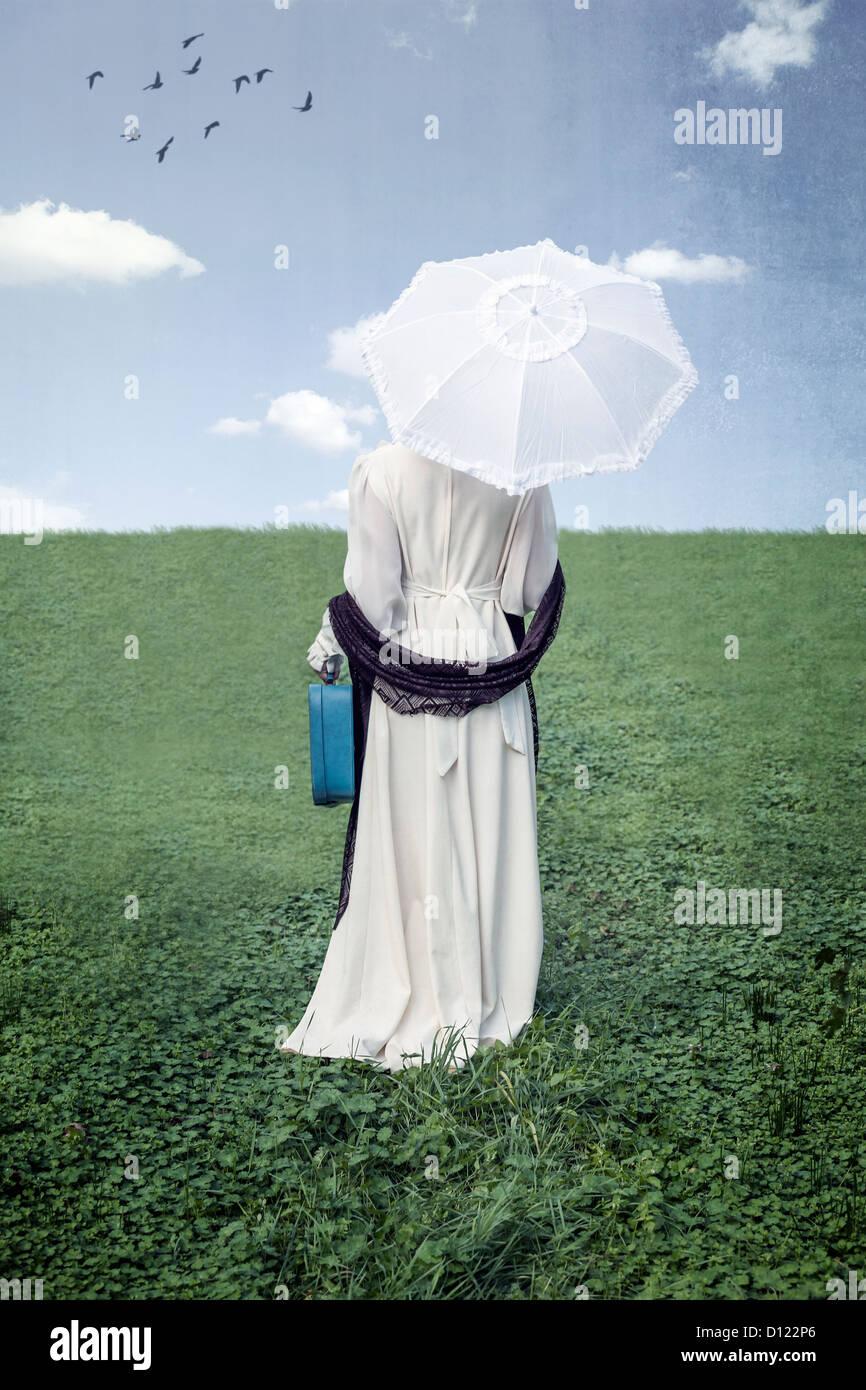 eine Frau mit einem Sonnenschirm und einem Koffer auf einer Wiese Stockbild