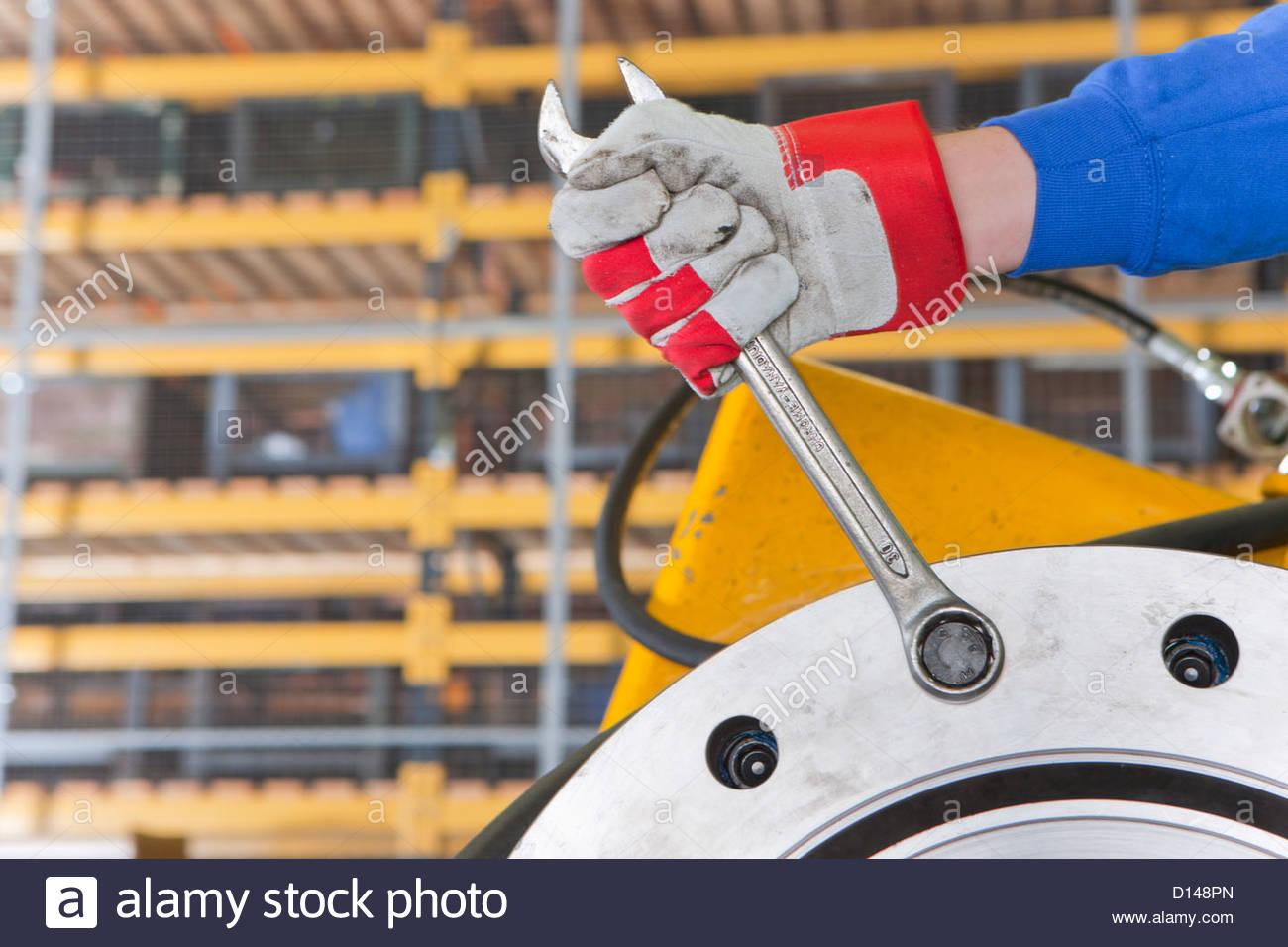 Nahaufnahme des Ingenieurs anziehen der Schraube am Getriebegehäuse in Fabrik Stockbild