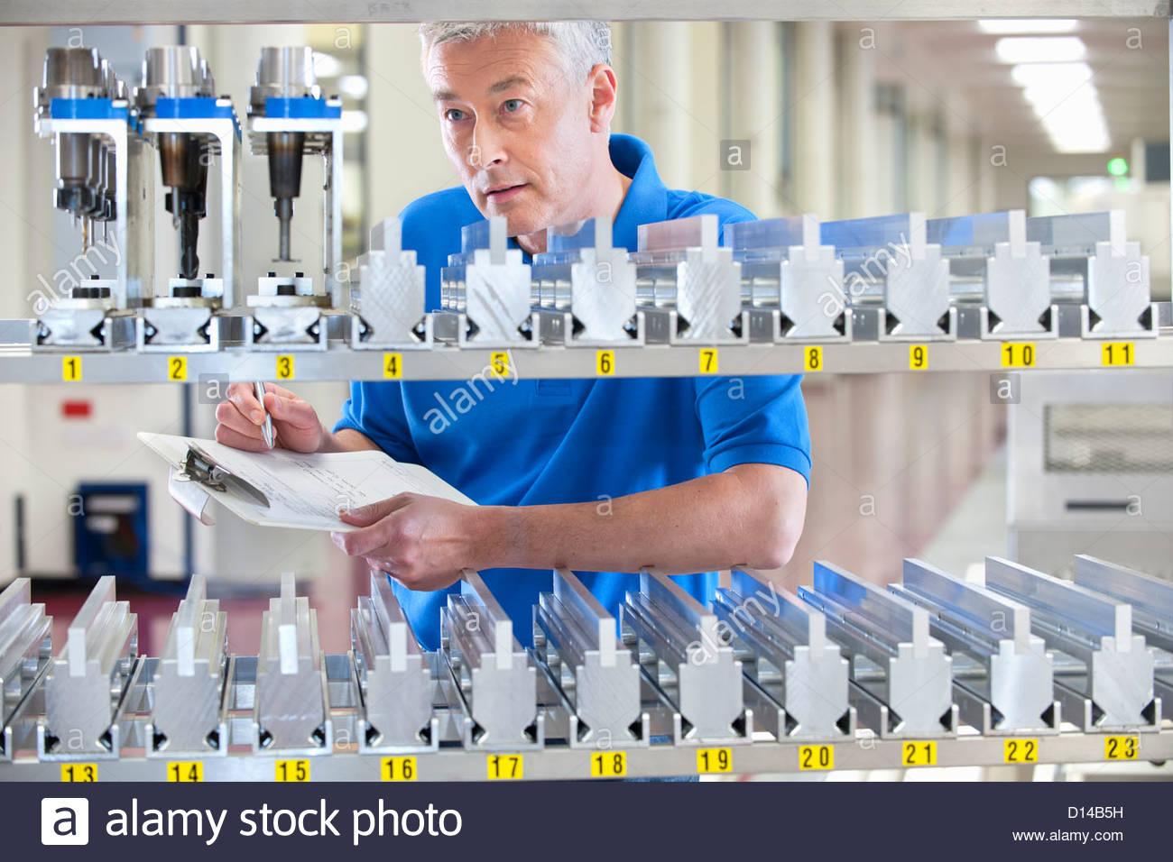 Techniker überprüfen Inventar von Maschinenteilen im Werksgelände Stockbild