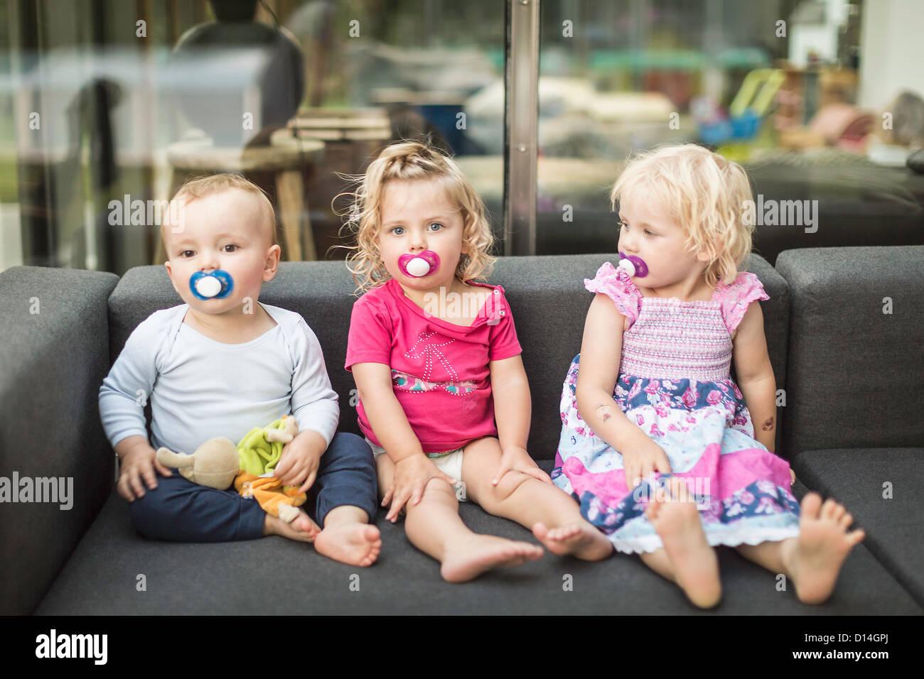 Kleinkinder, die zusammen am Schnuller saugen Stockbild