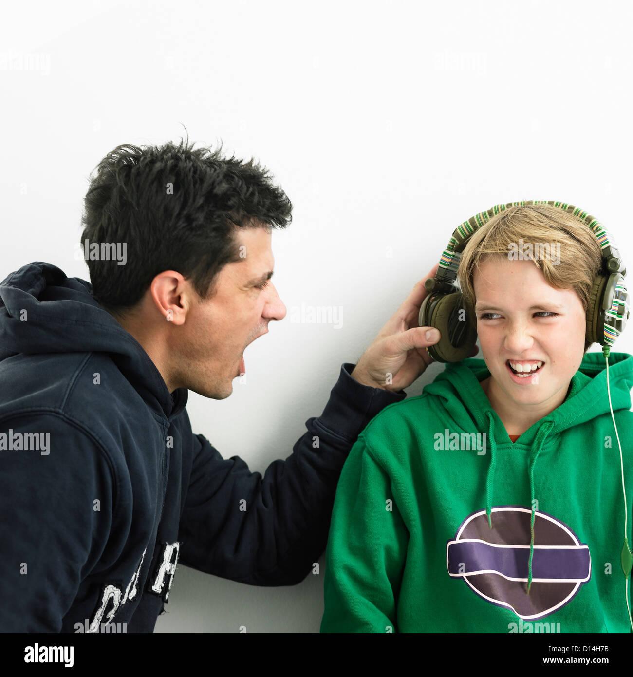 Vater in jungen Ohrhörer schreien Stockbild