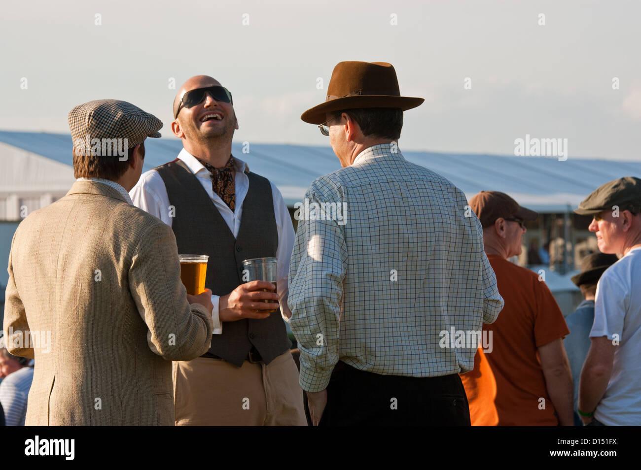 drei glückliche fröhliche Männer gekleidet in Vintage-Kleidung genießen ein Bier und ein Lachen Stockbild