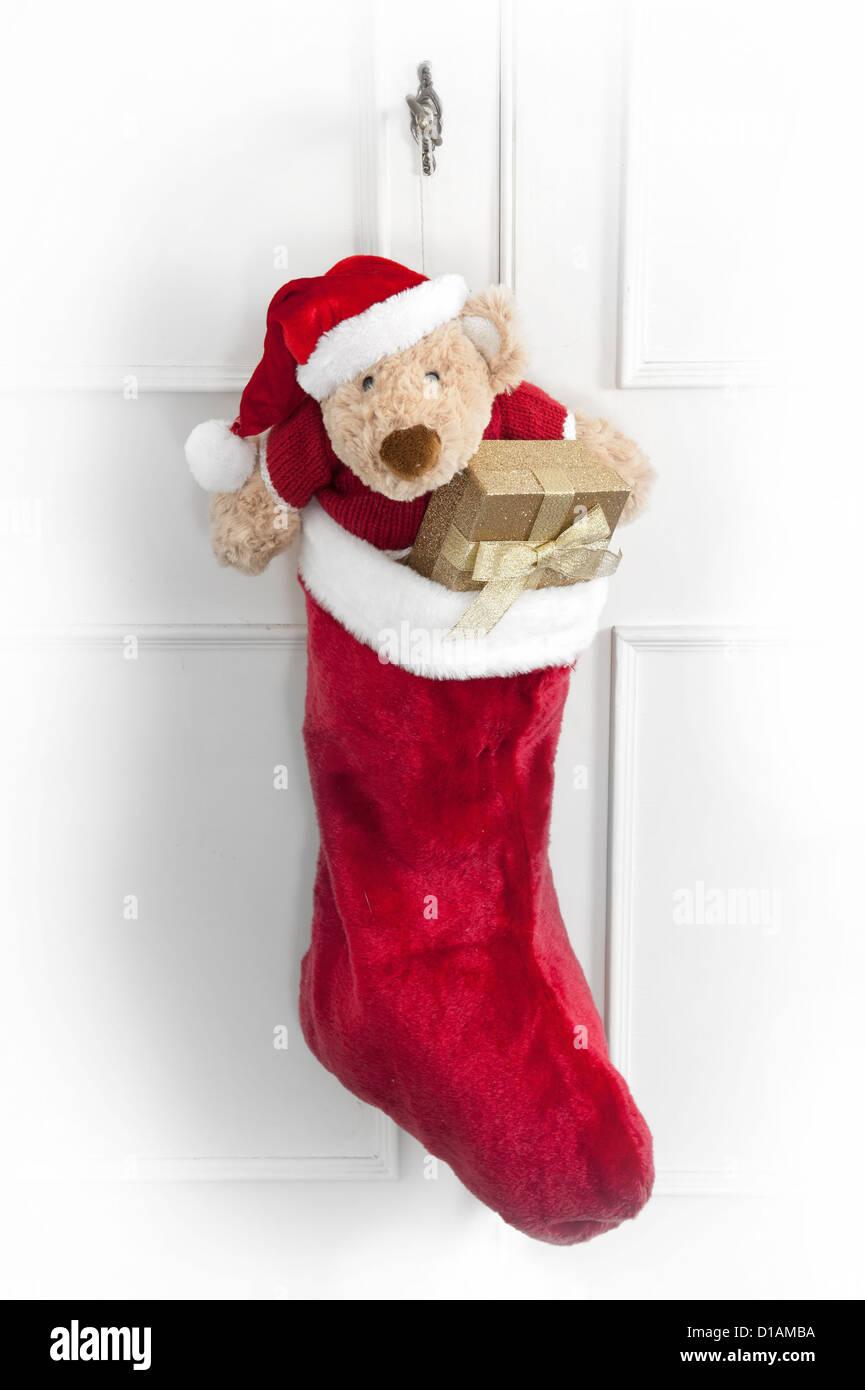 Weihnachtssocke mit Teddybär und Geschenke an eine Tür hängen ...
