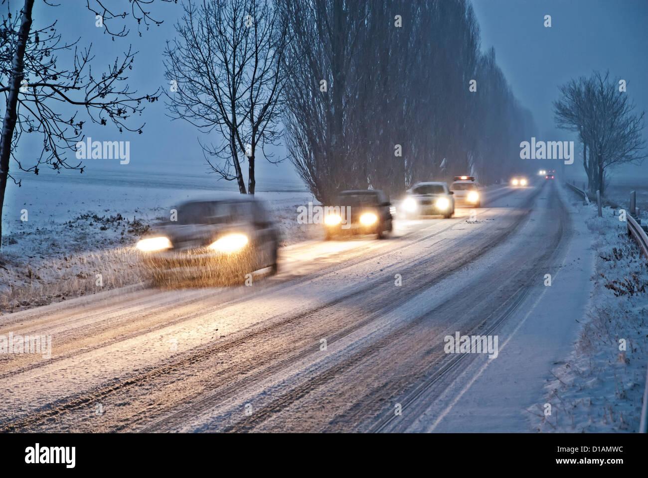 Autos in der Abenddämmerung auf einer verschneiten Landstraße in der Nähe von Bad Homburg im Taunus. Stockbild