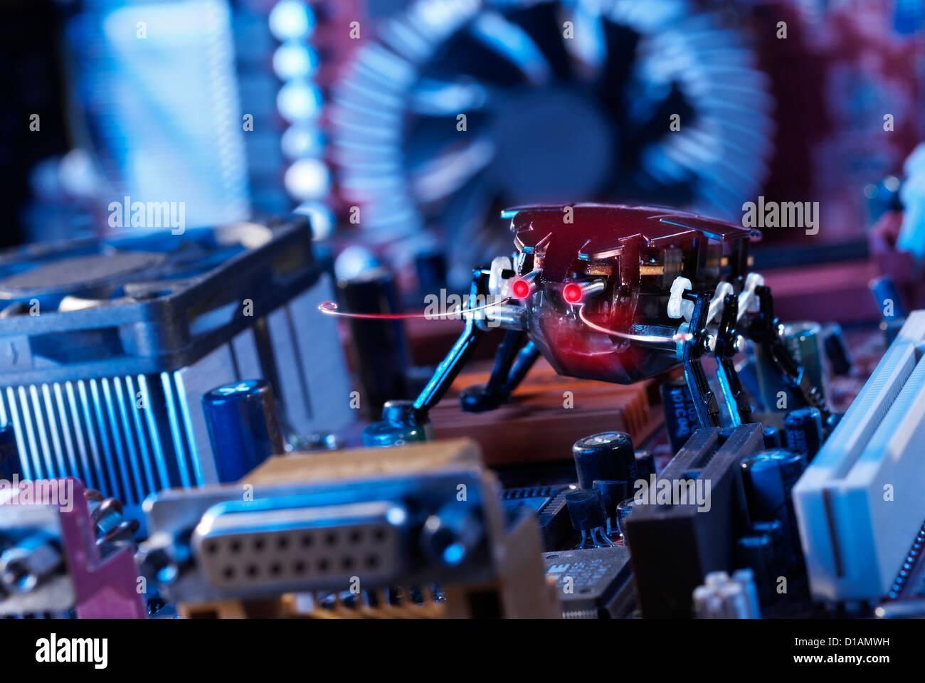 Ein Roboter Käfer mit rot glühenden Augen auf einem Motherboard. Stockbild