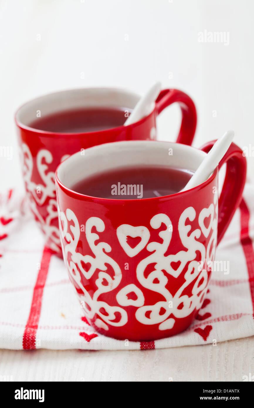 Weihnachten-Glühwein in zwei kleine rote Tassen ruht auf Teatowel ...
