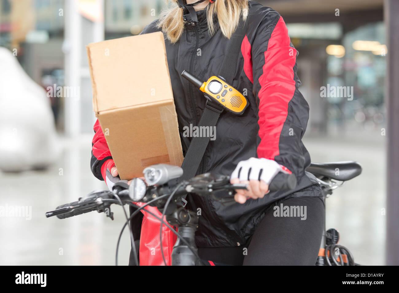 Weibliche Radfahrer mit Karton und Courier Bag auf Straße Stockbild