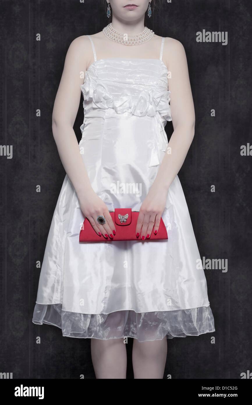 c07a072695295 Detailansicht einer Frau in einem weißen Kleid mit einer roten Handtasche  Stockbild