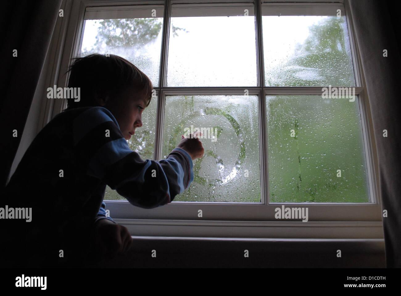 8 Jahre alter Junge zeichnen ein trauriges Gesicht in das Kondenswasser am Fenster. Stockbild