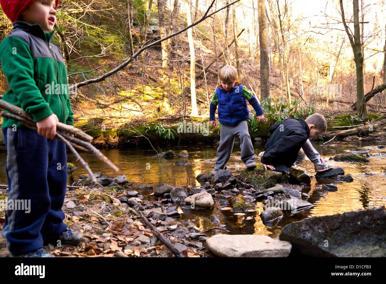 Drei kleine Jungs spielen in und um einen Stream an einem Herbsttag Stockbild