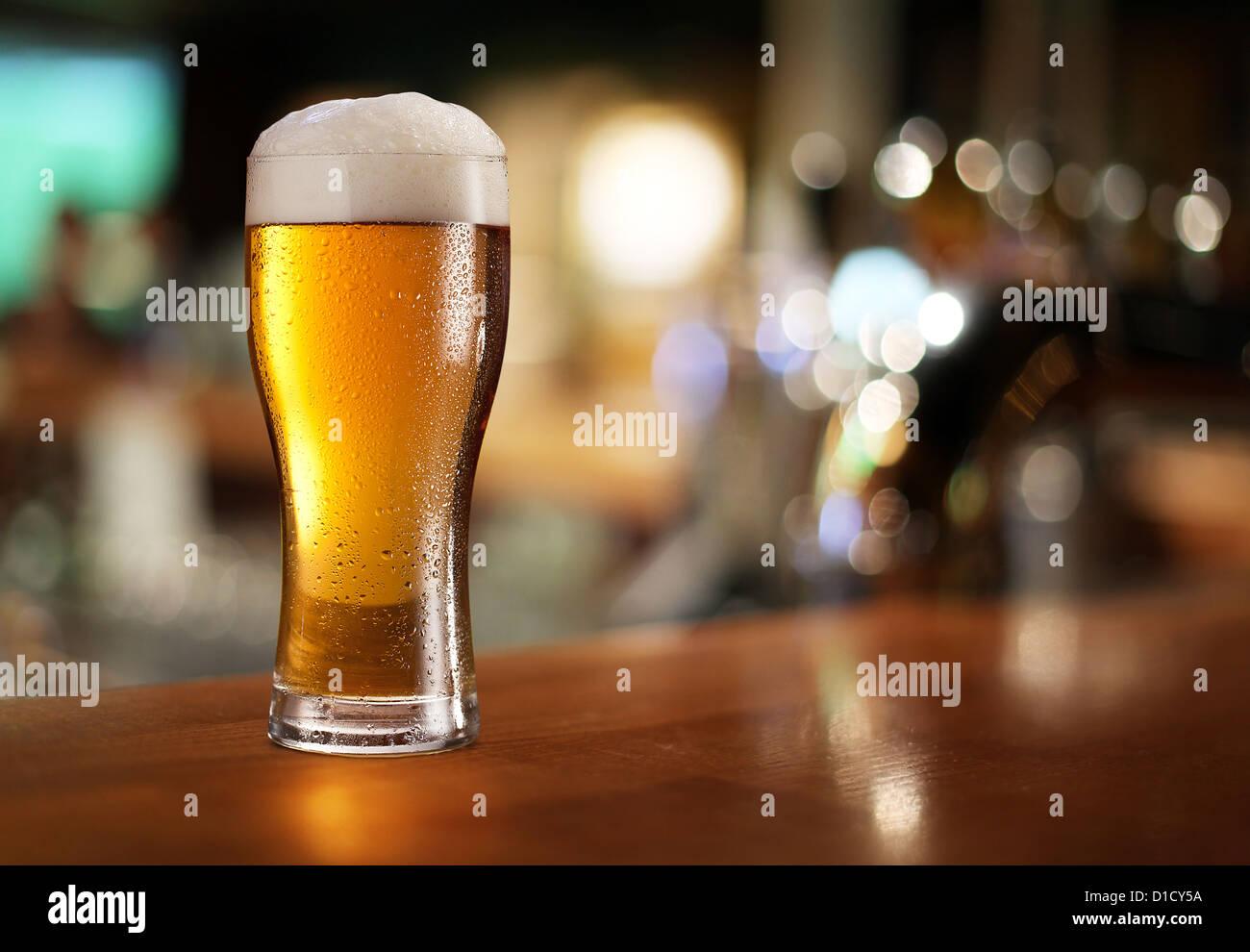 Glas helles Bier auf einer dunklen Kneipe. Stockbild