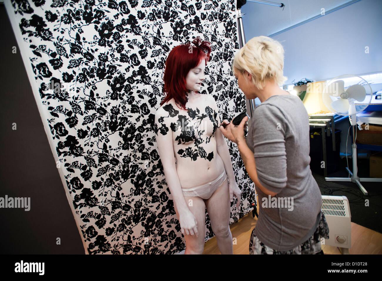 Eine junge Frau mit ihrem Körper gemalt eine schwarz / weiße Muster an den Hintergrund anpassen, die sie Stockbild