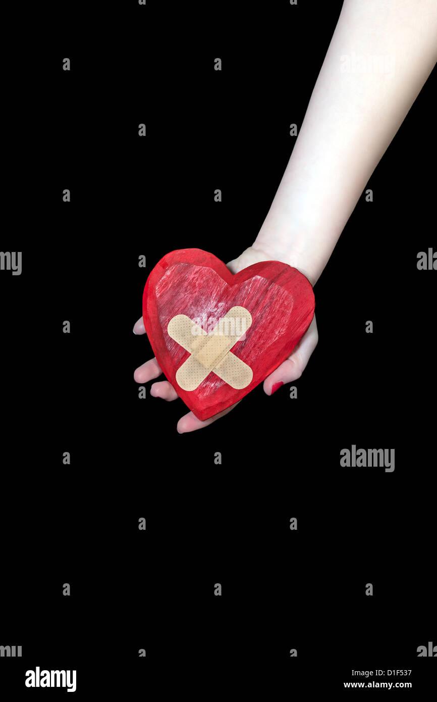 eine weibliche Hand hält ein gebrochenes Herz Stockbild