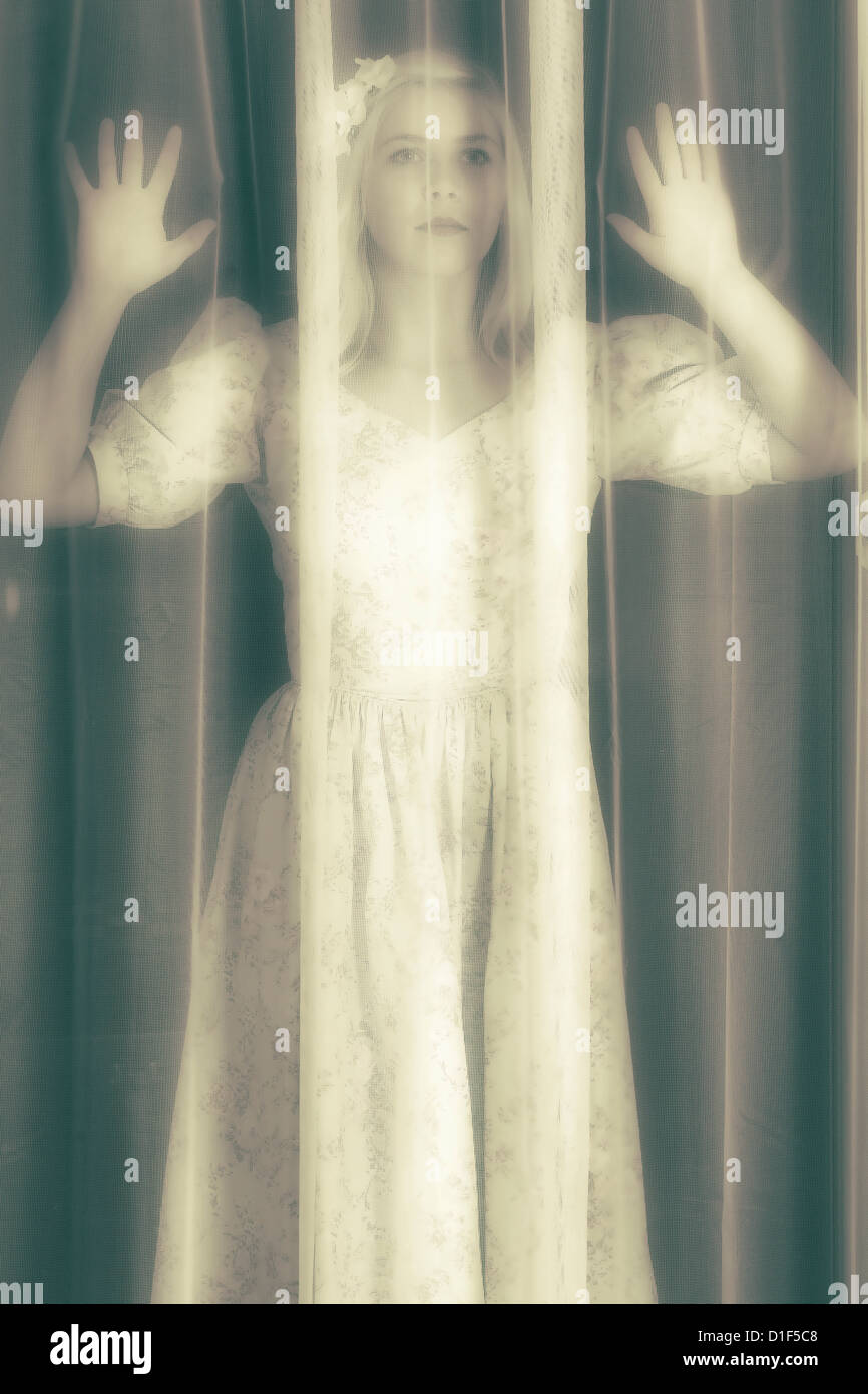 eine Mädchen sucht durch einen Vorhang Stockbild