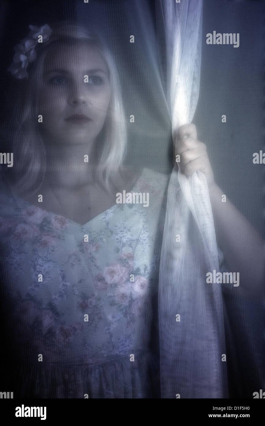 eine Mädchen ist hinter einem Vorhang versteckt. Stockbild