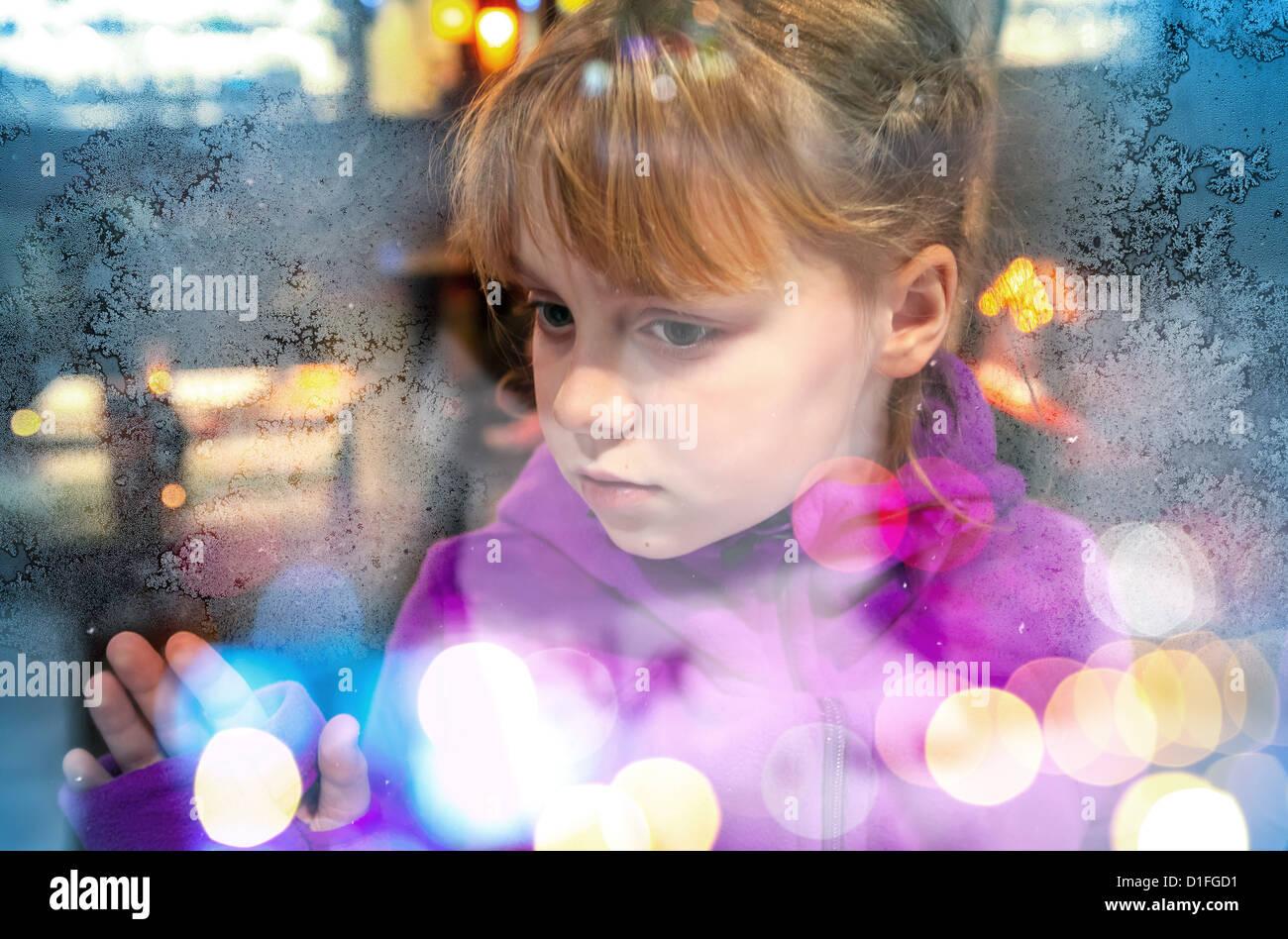 Kleines blondes Mädchen schaut durch gefrorenen Shop Fenster-Glas ...