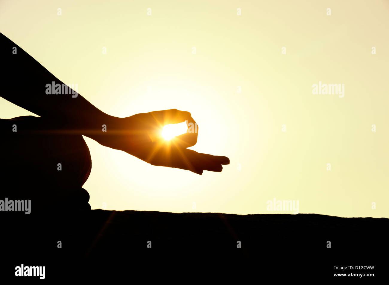 Sonnenuntergang Silhouette von einem indischen Mann meditiert. Andhra Pradesh, Indien Stockbild