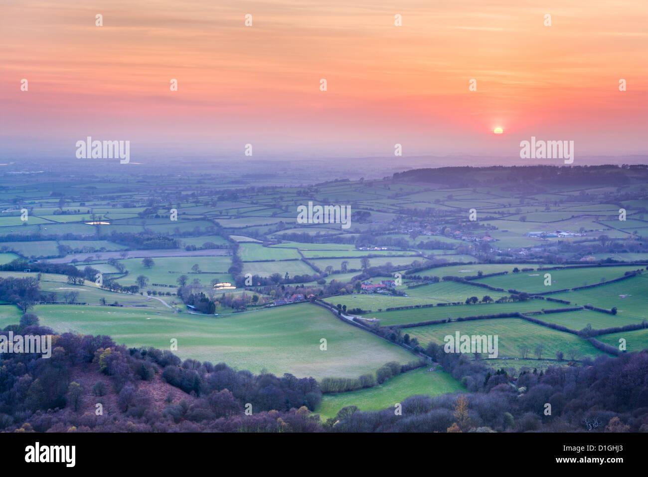 Einen farbenfrohen Sonnenuntergang von Sutton Bank durch den Aufbau von Vulkanasche aus Island, North Yorkshire, Stockbild