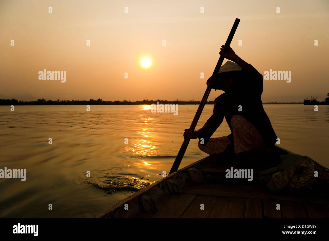 Alte Dame Rudern in Hoi an einen Hafen Silhouette bei Sonnenuntergang, Indochina, Vietnam, Südostasien, Asien Stockbild