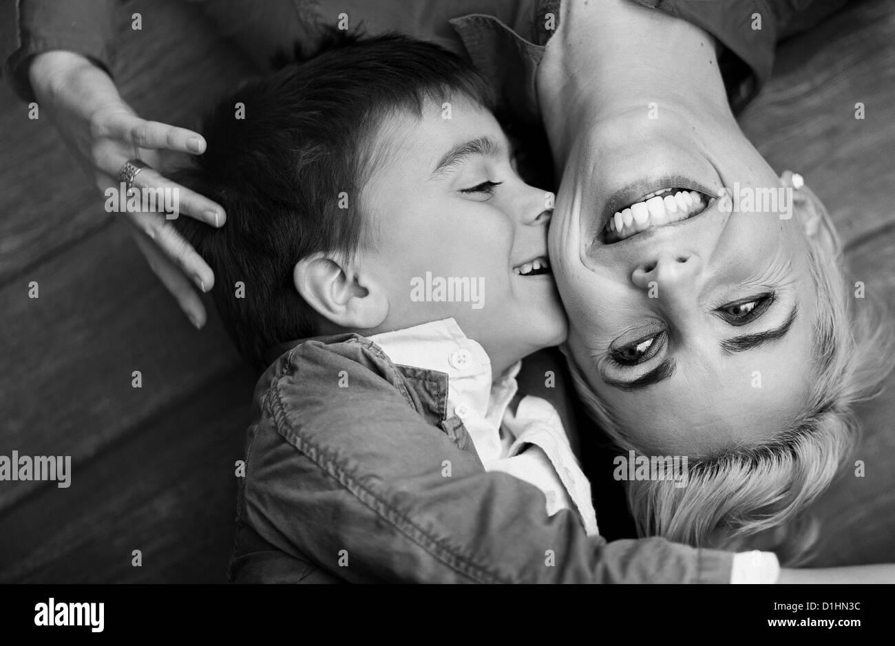 Hübsche Spross der niedlichen jungen küssen seine Mutter Stockbild