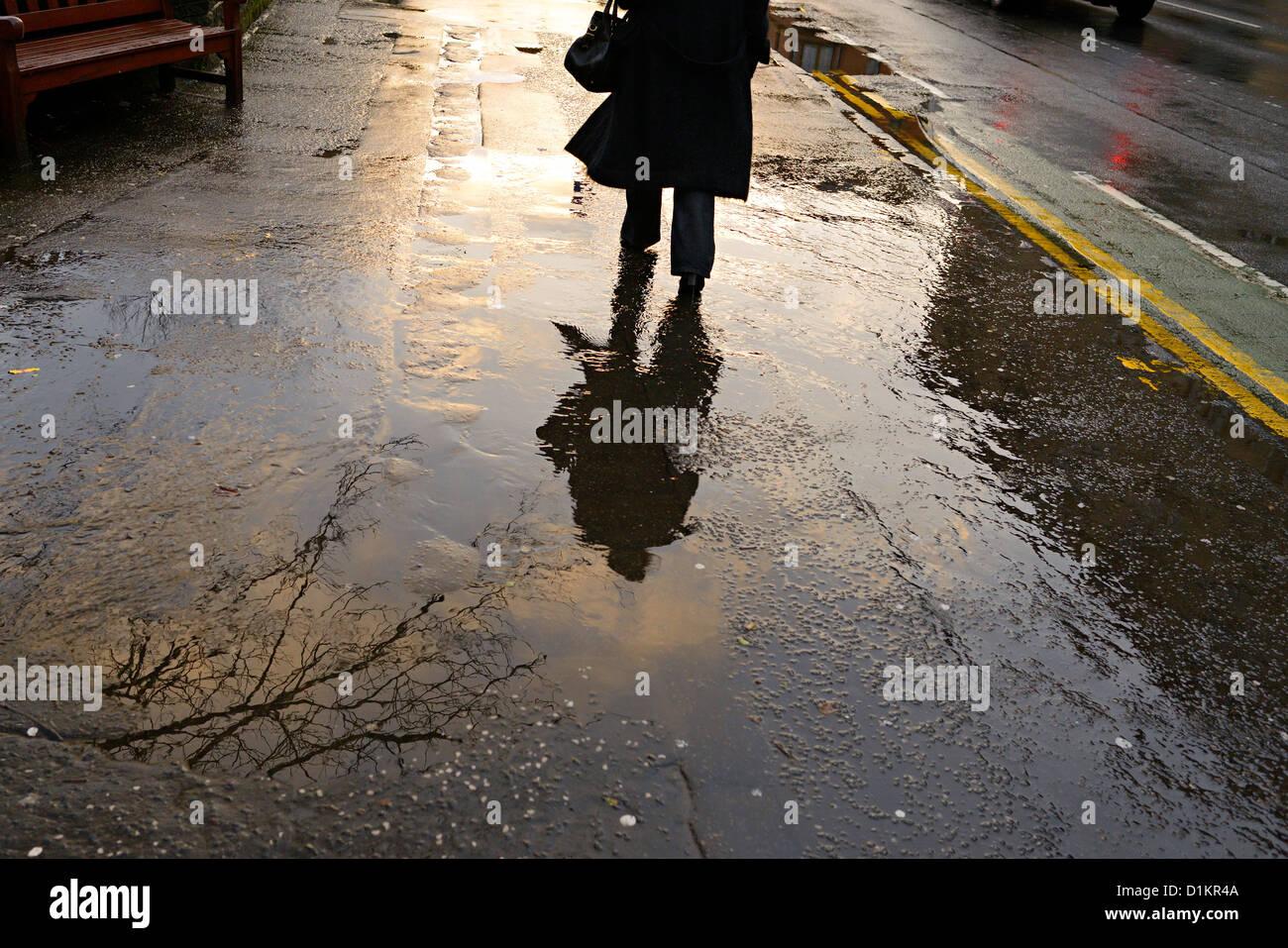 Frau in Glasgow geht Byres Straße im Regen Stockbild