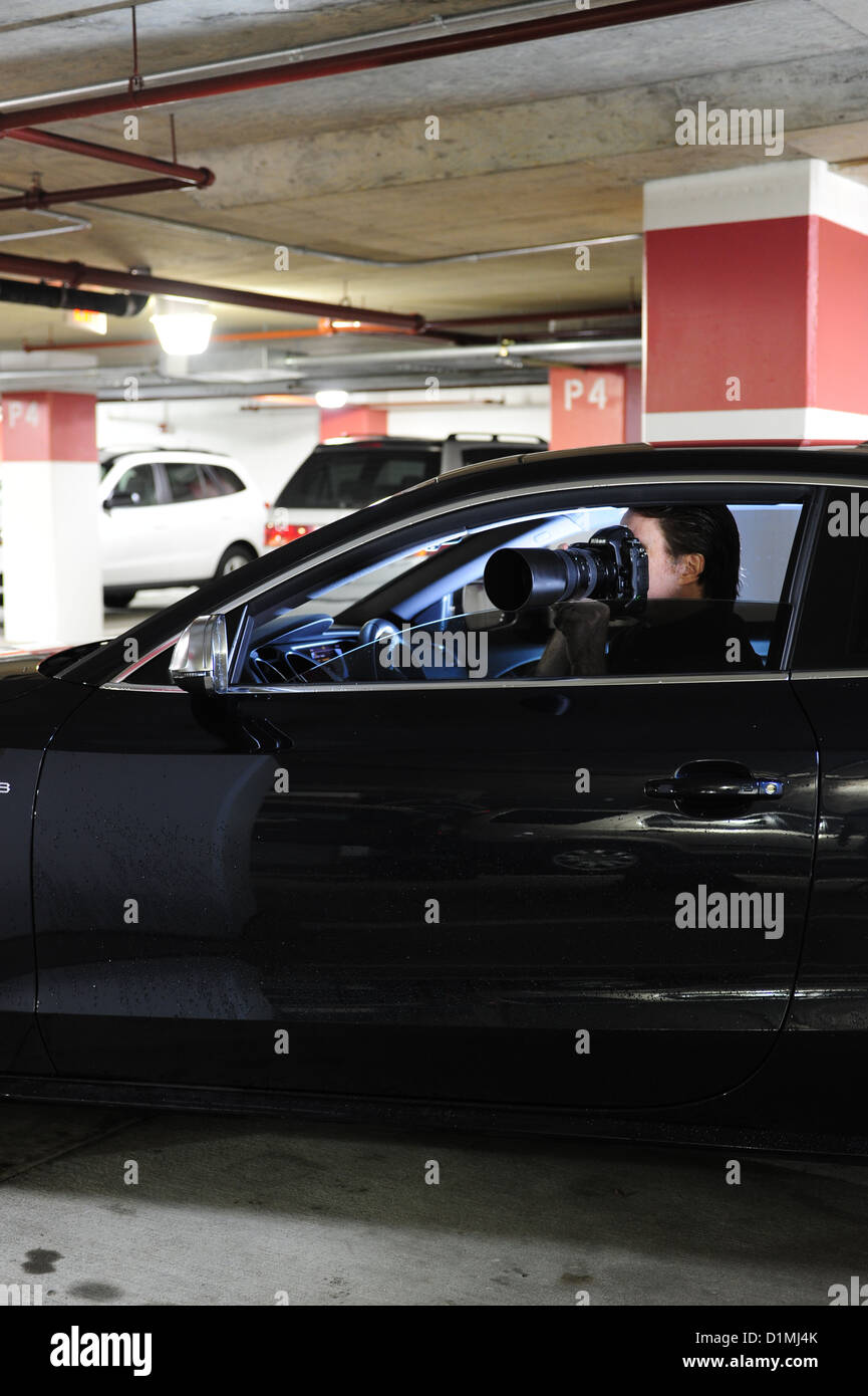 Privatdetektiv oder Privatdetektiv in Auto mit Kamera nach jemand heimlich Stockbild