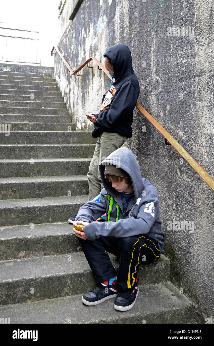 zwei Jungs im Teenageralter SMS mit Handys Stockbild