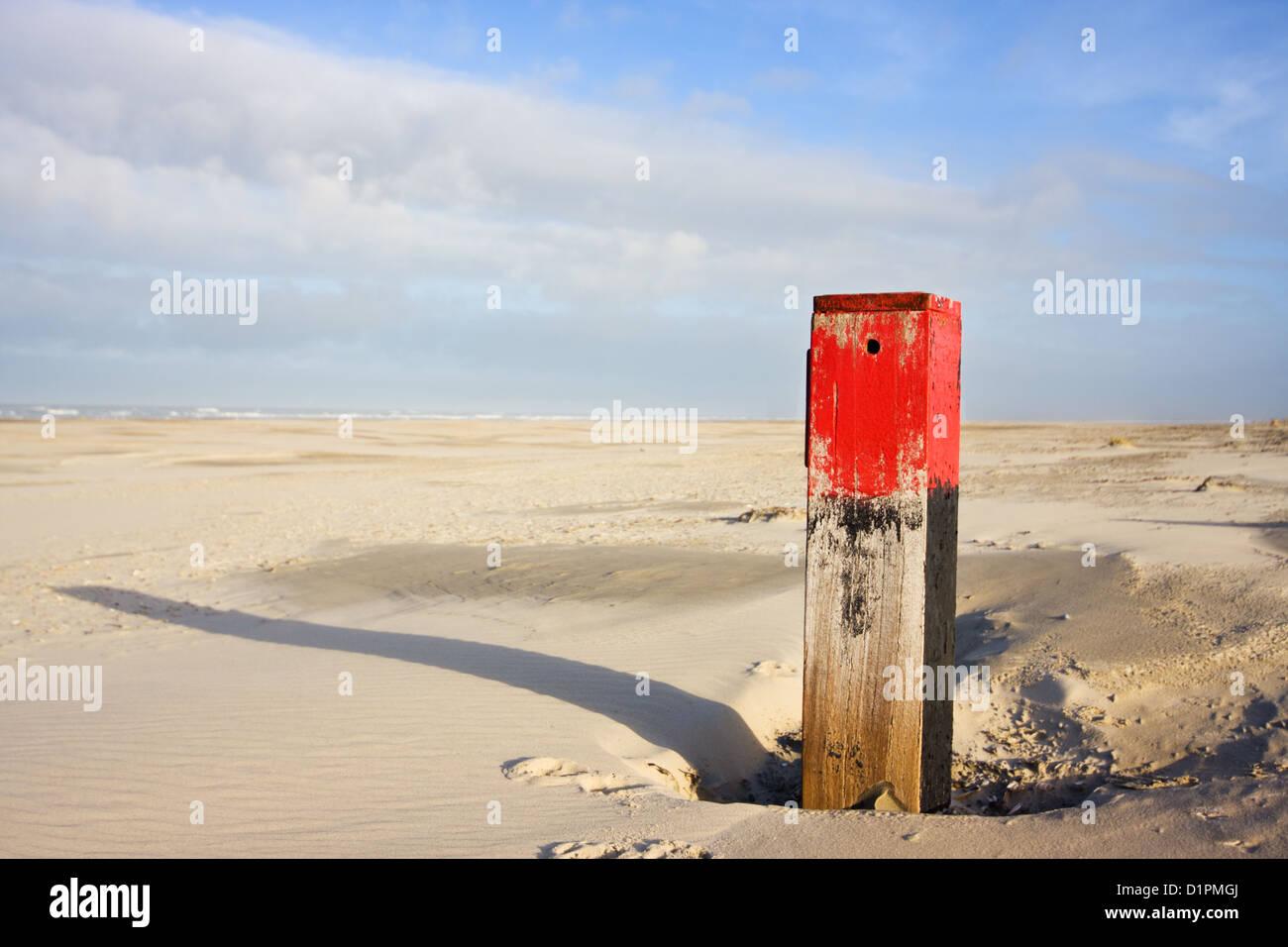 Roter Strand Pol mit langen Schatten auf riesigen Strand Stockbild