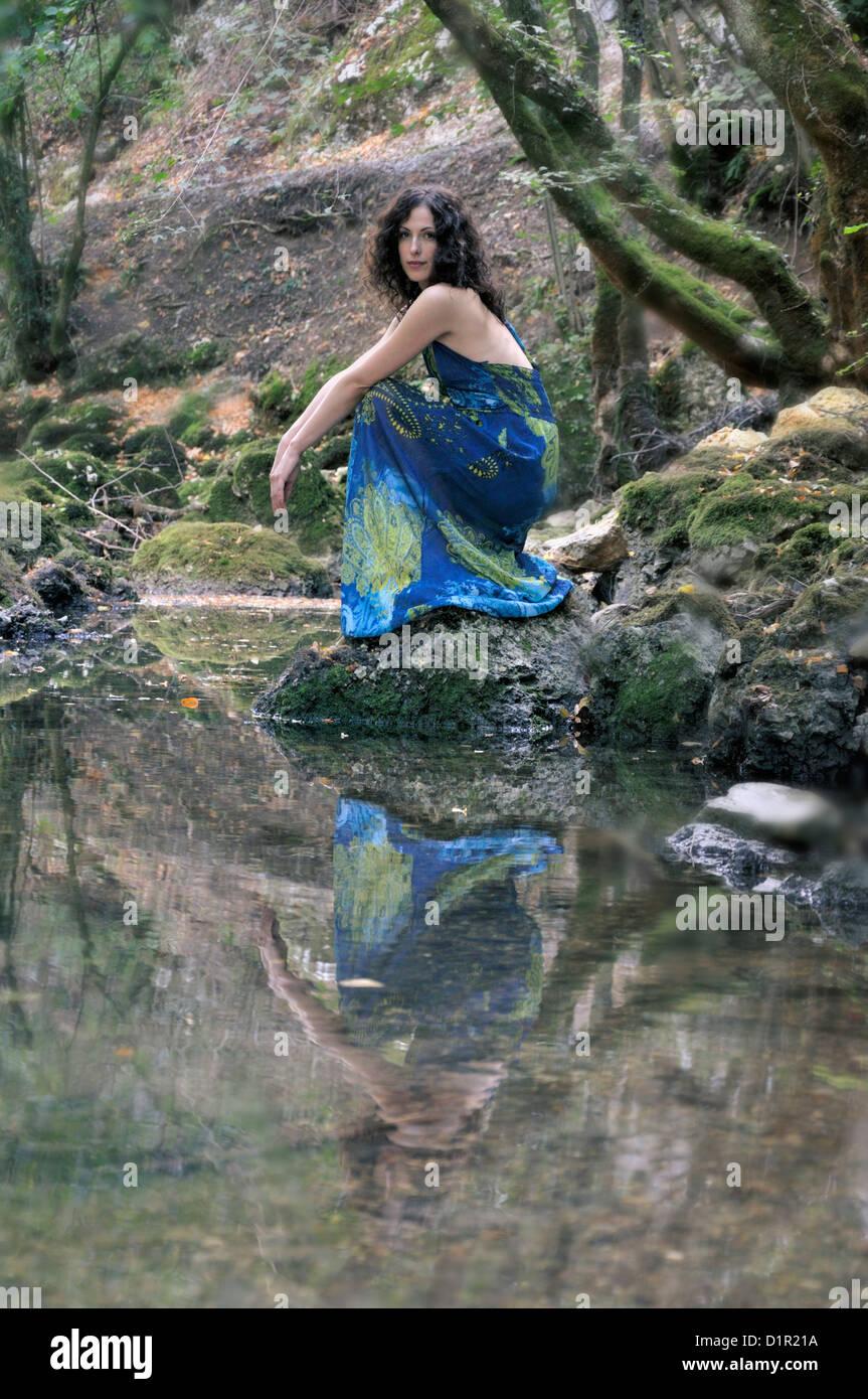 Junge schöne Frau kniend Fluss Stockbild