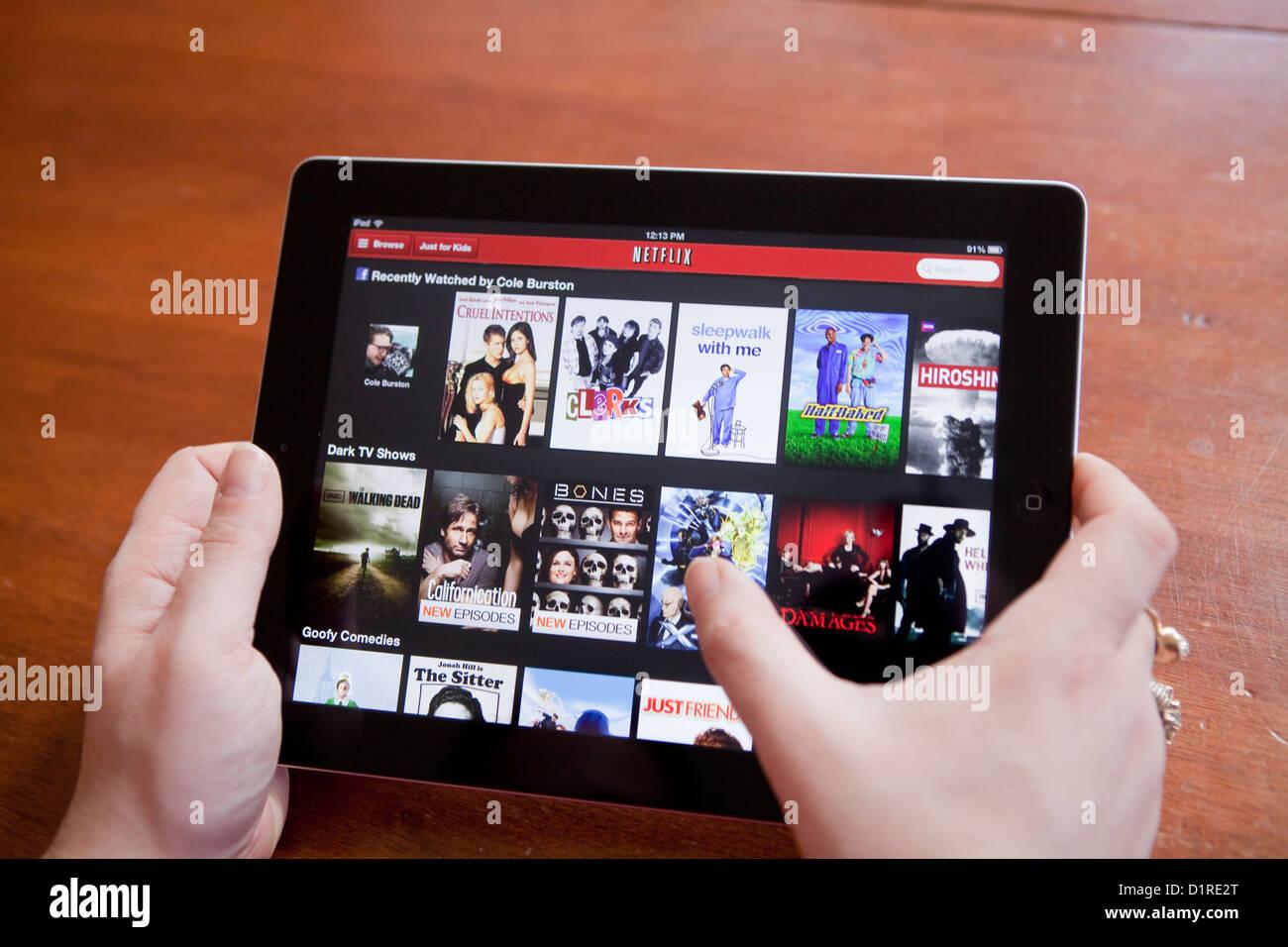 Eine Frau benutzt die Netflix-app auf dem iPad 4. Netflix, Inc. ist ein US-amerikanischer Anbieter von Anforderungs Stockbild