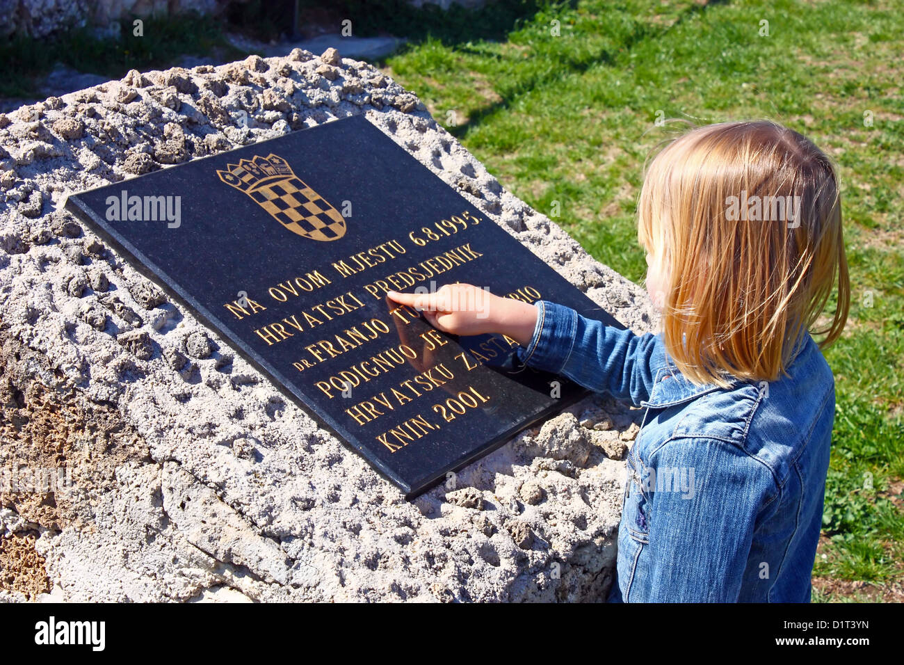 Kleines Mädchen liest Text aus Gedenktafel, Festung Knin Stockbild