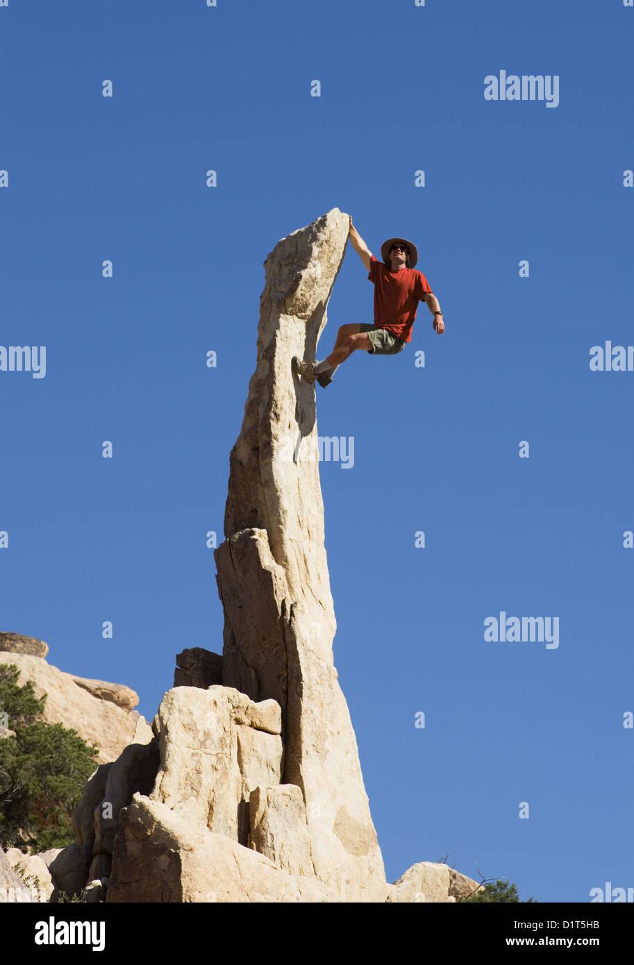 ein Mann klettert eine steile schmale Rock Turmspitze Stockbild